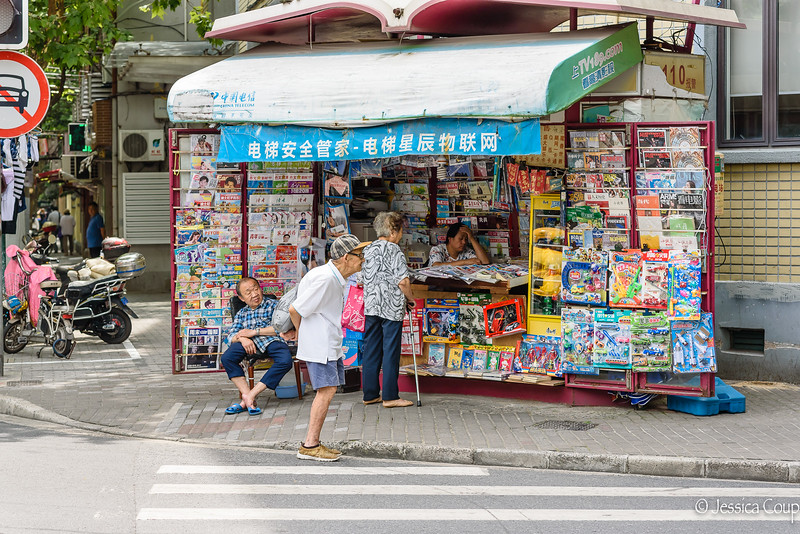 Watching Life Walk by at the Newspaper Stand