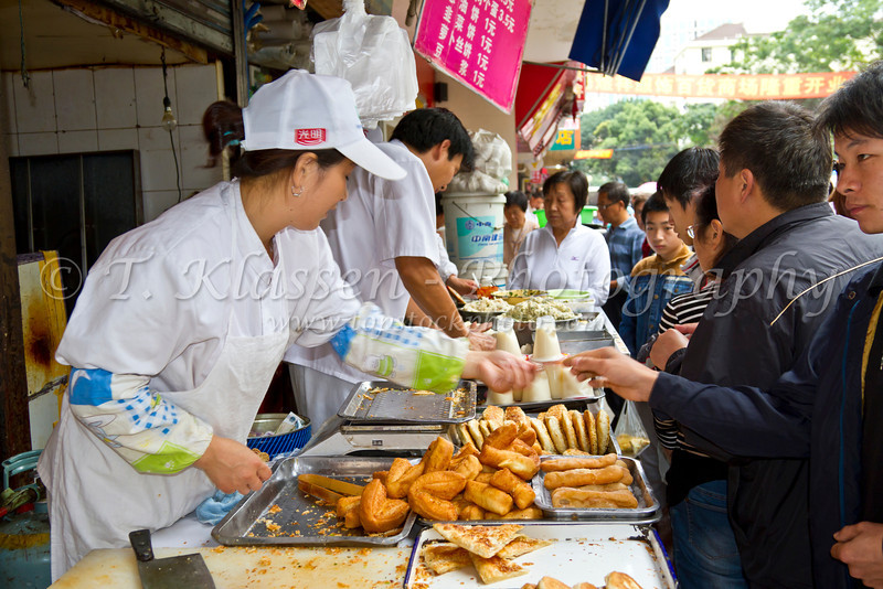 Street food being prepared at an outdoor street market in Shanghai, China, Asia.