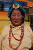 A decorated Tibetan woman at the bus stop