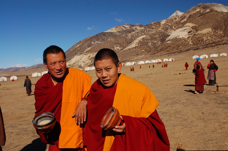Monks carrying their yak butter bowls