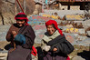 Tibetan women take a break from spinning prayer wheels