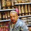 This fellow sells metal work, such as the vases seen on the shelves behind him.
