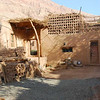 This is a typical home in Tuyogou: adobe construction plastered with mud, an outdoor oven and toilet, and miscellaneous sheep, goats, and chickens milling around.  The lattice structures on the roof are ventilated rooms for drying grapes.