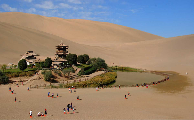 "Here is the goal of our camel ride: the oasis at Cresent Moon Lake.  This lake as been here for over 2,000 years and was a major stop on the Silk Road.  Marco stayed here and referred to the surrounding dunes as ""rumbling sands"" because of the sound they make when you walk on them."