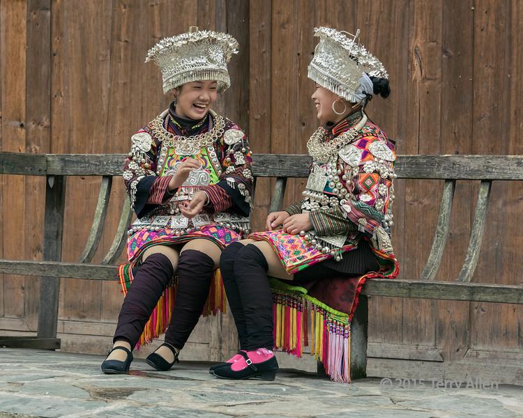 A-happy-moment,-Short-skirt-Miao-girls-on-a-bench,-Datang-Village,-Guizhou-Province,-China