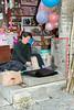 Woman vigorously pounding cloth to make it shine, Zhaoxing Dong village, Guizhou Province, China