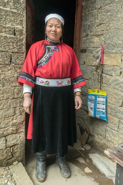Old-Han-(Tunpu)-woman-in-the-doorway-of-here-stone-house,-Liuguan-Han-Village,-Guizhou-Province,-China
