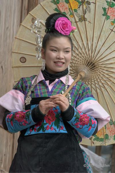 Smililng Miao girl with umbrella, Shiqiao Miao Village, Guizhou Province, China