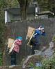 Women-carrying-heavy-baskets-of-gravel-up-to-a-construction-site,-Malizai-area,-Yuanyang,-Yunnan,-China