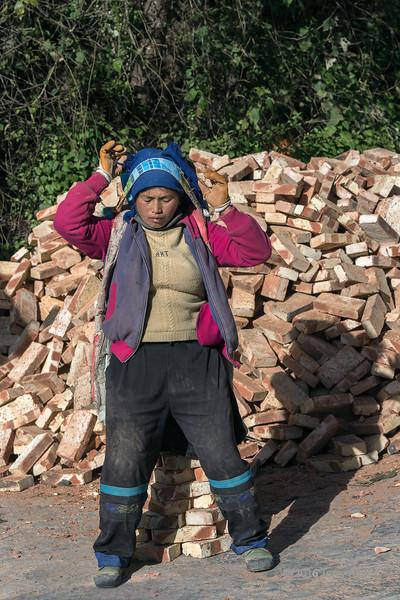 Woman-labourer-picking-up-a-stack-of-bricks-with-a-trumpline,-Bada,-Yuanyang,-Yunnan-Province,-China