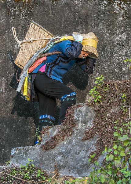 Woman-construction-worker-hauling-a-basket-full-of-gravel,-Malizai-area,-Yuanyang,-Yunnan,-China