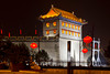 Pagoda architecture and city gate along the wall in Xian, China illuminated at night.