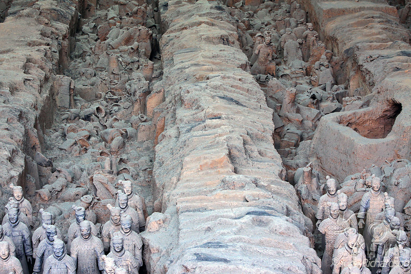 Fragments of Terracotta figures lie in pits with indentations where timbers once covered them