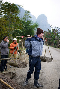 My friend Pete convinces the workers to let him try out their heavy load, rural Yangshuo, China.