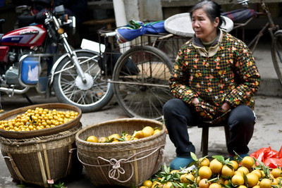 A vendor quietly watches as the locals peruse the vegetable stands and pick out their dinner at the Fuli Market near Yangshuo, China.