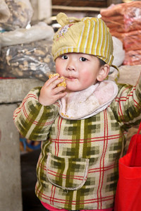 A wee one catches sight of the only foreigners at the market and watches us carefully, Fuli Market near Yangshuo, China.