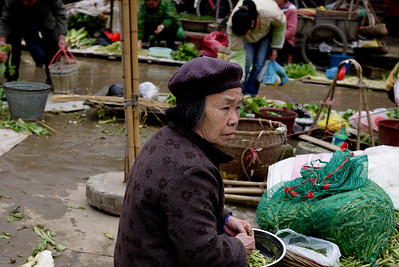 Women and men line the market area with their fresh fruits and vegetables.