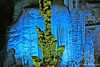 Green Statue of Stalagmites with Blue mountains of Stalactites behind