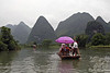 Pretty in pink bamboo raft with scenic Karst beyond