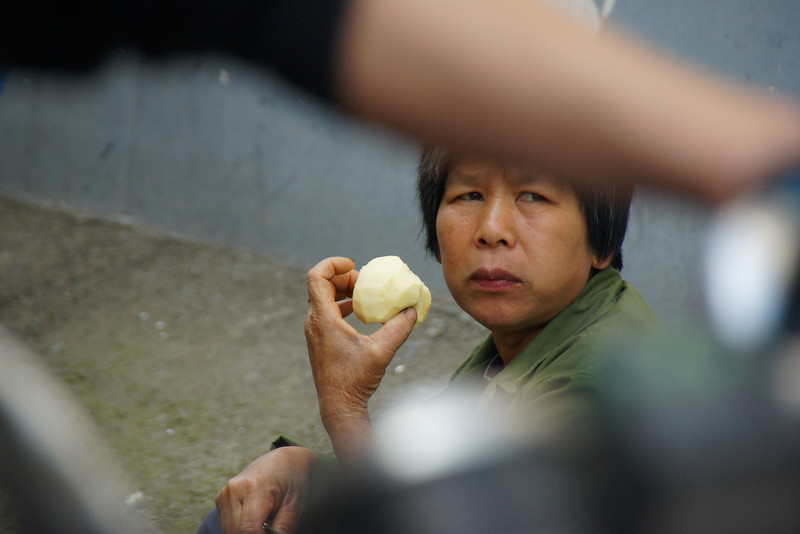 """Today's daily travel photo is of a Chinese lady eating an apple in a hectic street area of Yangshuo, China framed by a motion blurred bicycle:<br /> <a href=""""http://nomadicsamuel.com/photo-blog/lady-eating-apple-yangshuo-china"""">http://nomadicsamuel.com/photo-blog/lady-eating-apple-yangshuo-china</a>"""