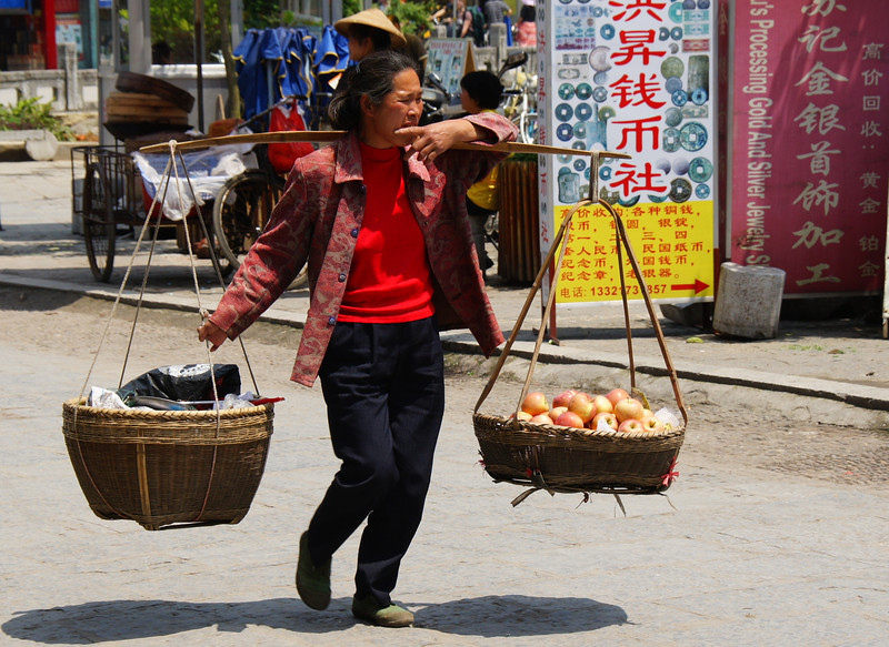 Today's daily travel photo is of a Chinese lady carrying a yoke filled with apples and other supplies on a warm afternoon in Yangshuo, China.