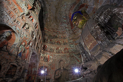 "YUNGANG CAVE 5, SHANXI, CHINA All over the inner surface of the Cave are carved with niches and Buddhist statues.  At either side of the Cave arch door, with fine relief sculpture of ""Flying Apsaras"" at the top, is a Buddha statue in sitting posture under the bodhi tree."