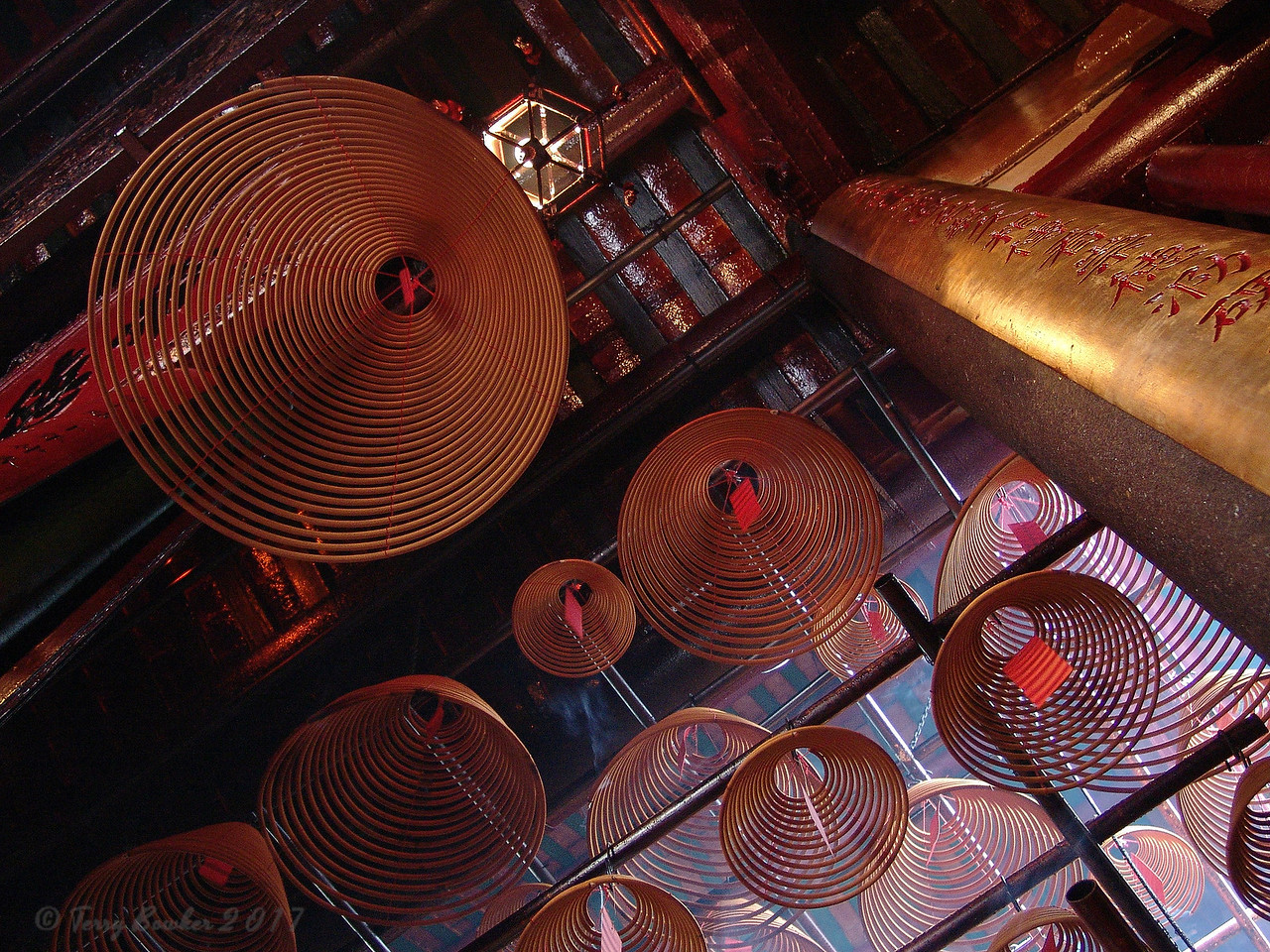 Incense Coils Hanging In Man Mo Temple, Hong Kong.  Hong Kong Island's oldest and most important temple (Taoist) was built in the 1840s as one of the new colony's first traditional-style temples. It's named after its two principal deities: Man, the god of literature, who is dressed in red and holds a calligraphy brush; and Mo, the god of war, wearing a green robe and holding a sword.