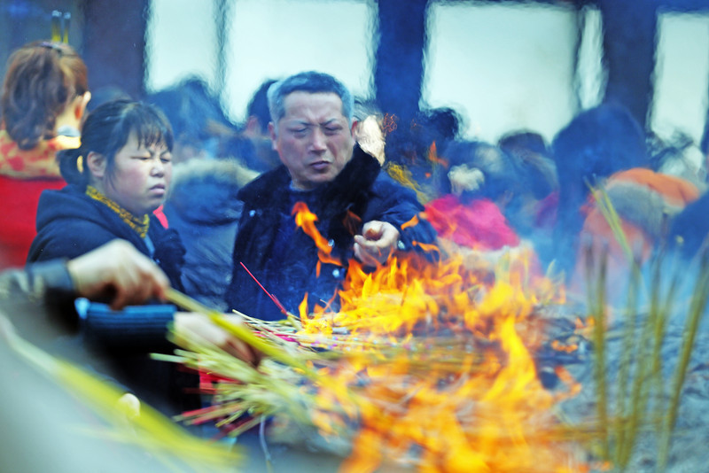 Burning incense during the Qīngmíng festival in the Jiming (鸡鸣寺) Buddhist Temple, Nánjīng, China