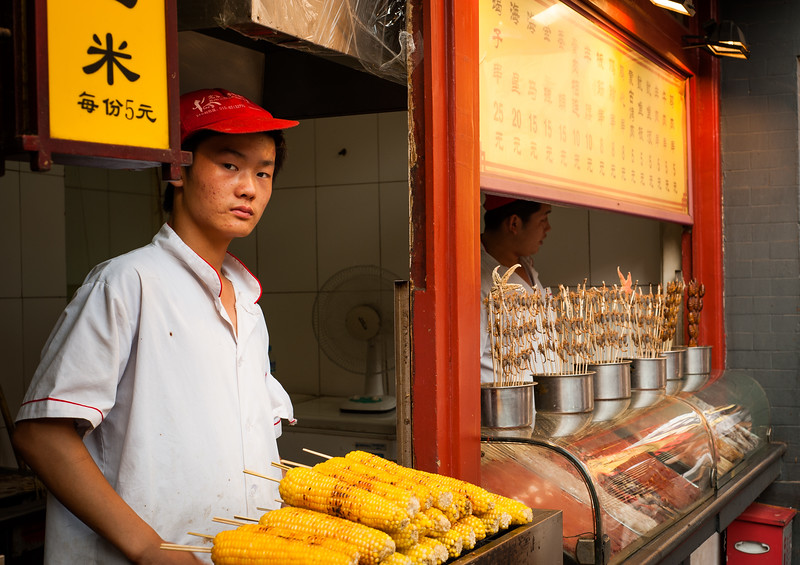 Male street vendor selling sweetcorn and scorpions, Beijing, China