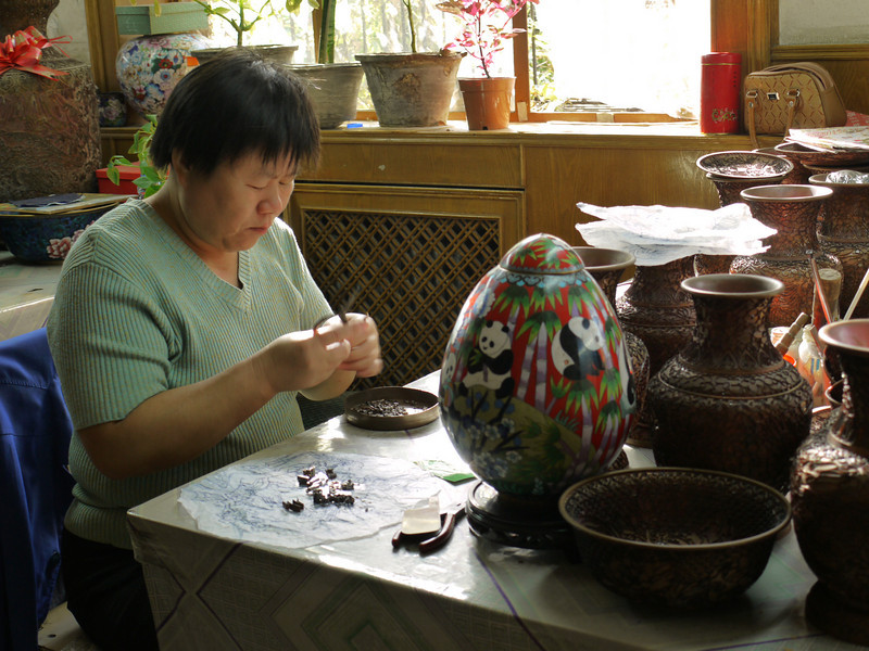 To  make cloisonne, you start with a bowl, dish, or vase made of thin copper.  Then apply wire shapes with secret herbal glue.  This woman is making shapes by bending copper wire to match a pattern.