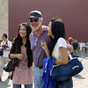Tall Chinese girls clamor for a photo with a tall bearded American.