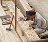 A craftsman works on carvings.