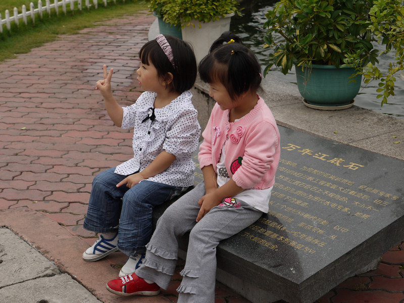 Little girls gotta pose for pictures -- sitting on the sign describing the Three Gorges Dam.