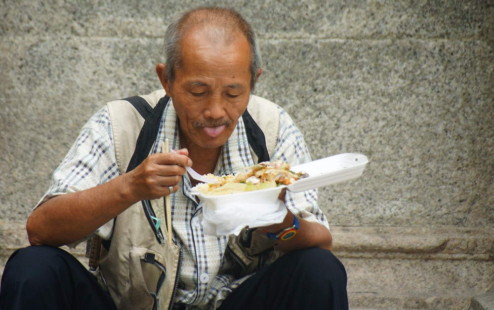 Man sitting down to eat Macanese cuisine