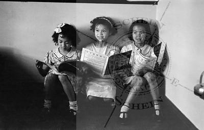 3 Merchant Kids, girls reading the News