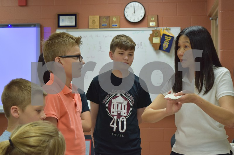 Instructor Linda Ma shows how to form traditional Chinese dumplings Friday during Startalk's Chinese language immersion program. The sixth annual three-week summer camp for students that have completed third through eighth grades runs through June 30 at DeKalb High School.