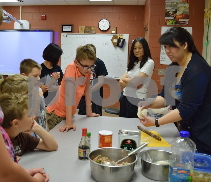 Agnes Ma (right) and her mother Linda Ma show how form traditional Chinese dumplings Friday during Startalk's Chinese language immersion program. The sixth annual three-week summer camp for students that have completed third through eighth grades runs through June 30 at DeKalb High School.