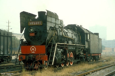 """Near the """"New"""" steelworks at Tangshan, our group encountered our first sightings of the JS class 2-8-2s of the tour. This example, JS 5992, was the first I had seen fitted with high smoke deflectors, and is depicted here in light steam at the China Rail exchange sidings. 29th October 1998"""