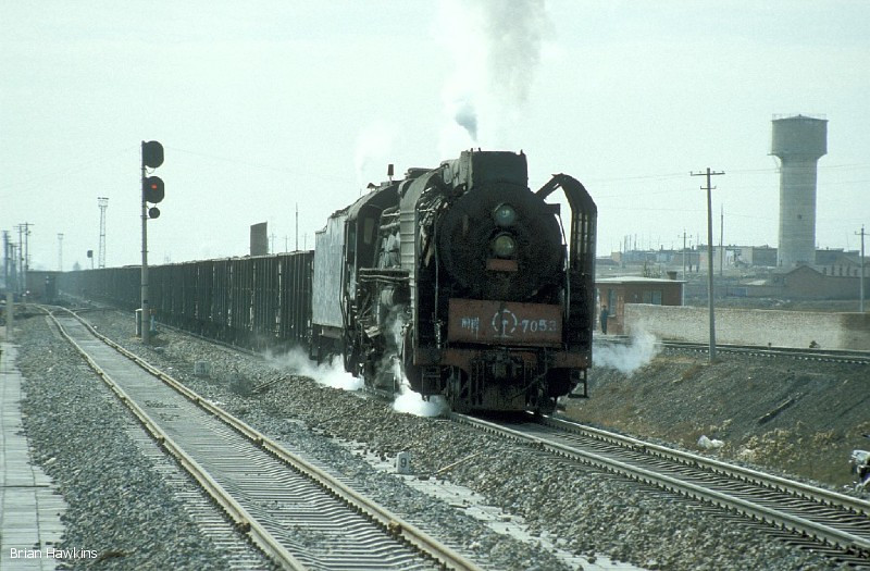 QJ 7053 departs from Dongsheng yard with a rake of coal empties. 1st November 2001
