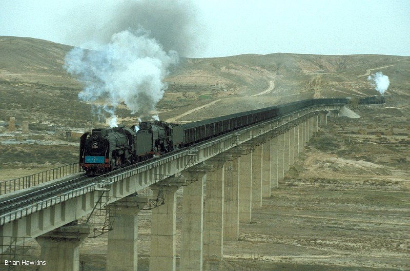 QJ 6784 + QJ 6178, with QJ 6404 banking, cross one of the many spectacular viaducts on the Baotou - Shenmu Bei Railway with a coal train near Aobaogou. 30th October 2001