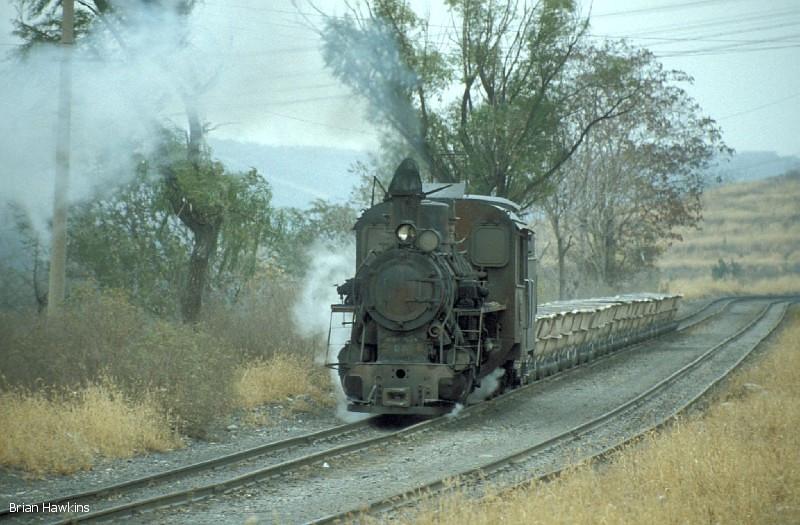 C2 class 0-8-0 No. 4 hauls empty tub wagons towards the quarry on the 762 mm Daihuichang Limestone Railway. 3rd November 2001