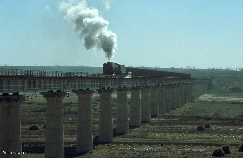 QJ 2938 is down to walking pace with its heavy train near Aobaogou. The Baotou-Dongsheng-Shenmu Bei line opened in the early 1990's for the main purpose of coal tranportation from the coalfields near Shenmu to Baotou. 31st October 2001