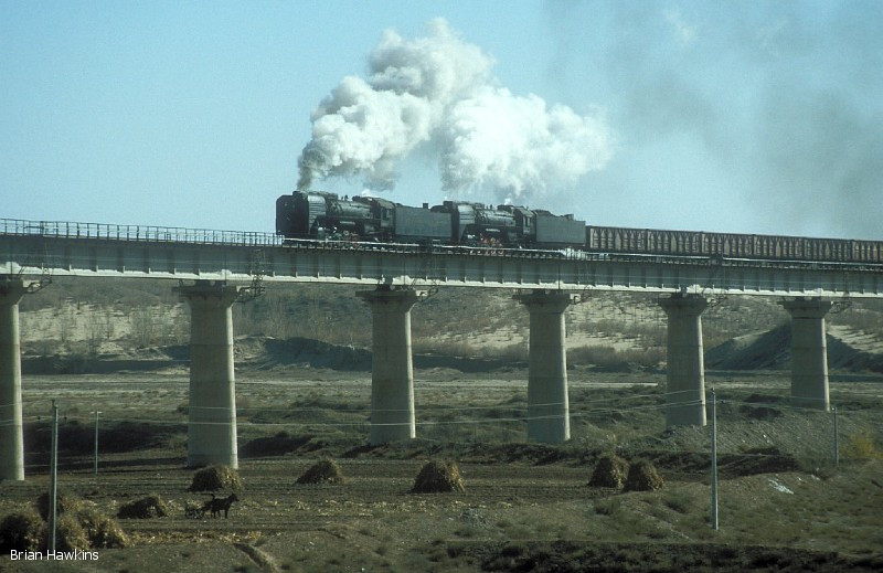Several impressive viaducts, as well as 3000-ton coal trains requiring three QJ 2-10-2 locomotives, were a feature of the Baotou-Shenmu Bei Railway. Here we see one of these coal trains with QJ 6287 and QJ 6088 in charge near Aobaogou. 31st October 2001