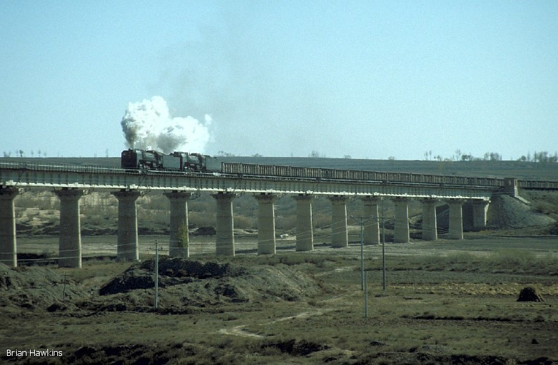 QJ 6287 + QJ 6088 haul another heavy coal train over a long viaduct near Aobaogou on 31st October 2001. Steam finished on the Baotou-Dongsheng-Shenmu Bei line in June 2002