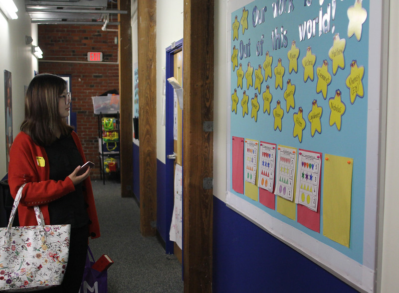 Lynn, Ma. 9-18-17. Claire Meng, a school principal from China, about to photograph a bulletin board in the hallway of KIPP during her tour of the building.