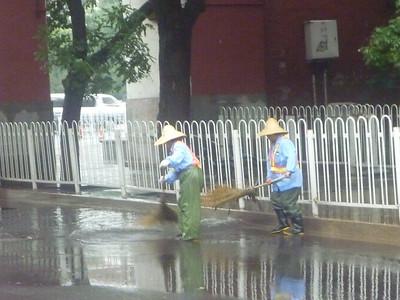 Panie zamiatają wodę z ulicy