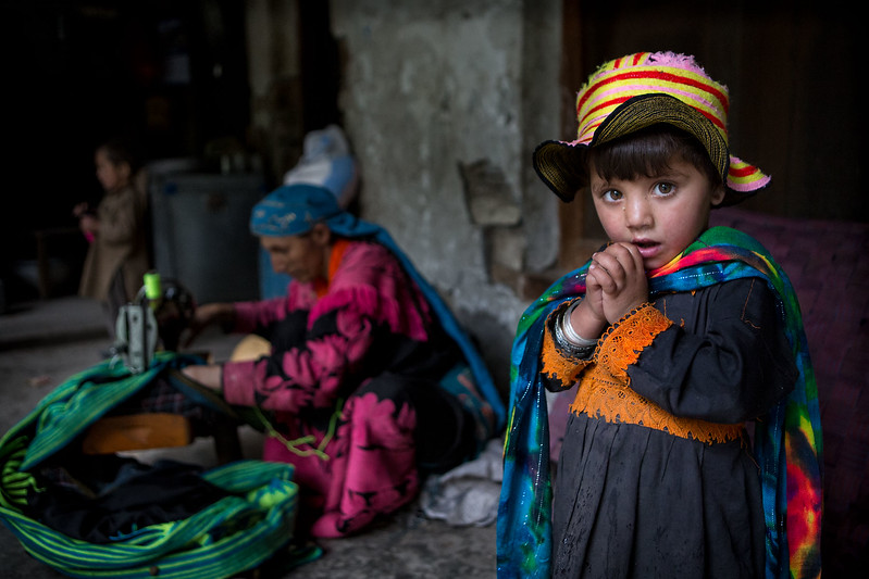 A small Kalasha girl with her mother working and her brother in the background.
