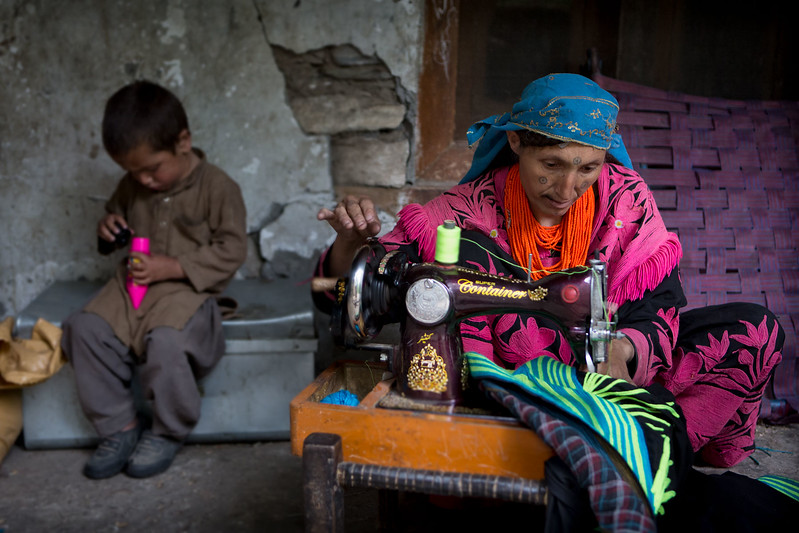 A Kalasha woman working with her son in the background.