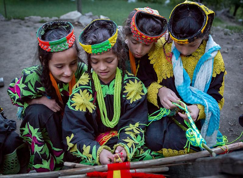Young Kalasha girls weaving.