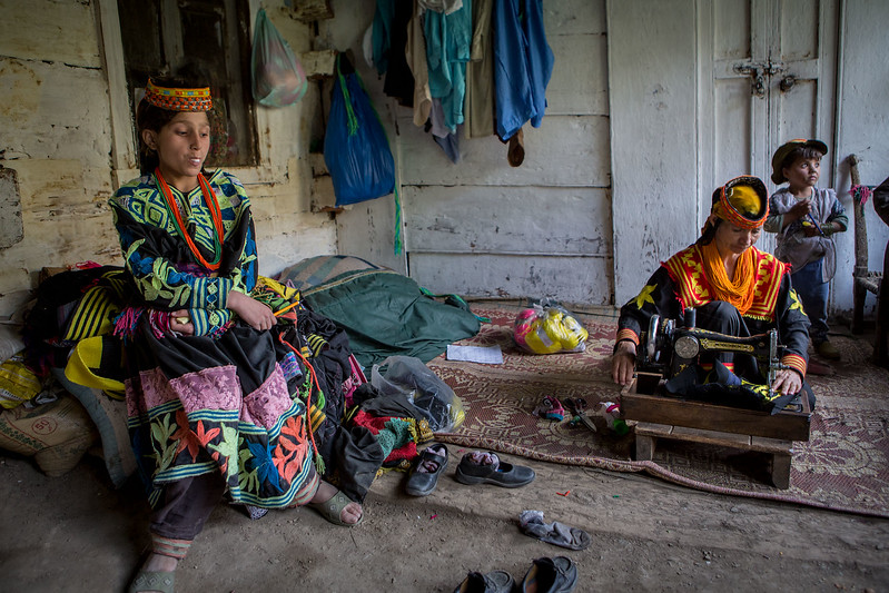 A Kalasha girl. Her mother is sewing a new kalash dress.